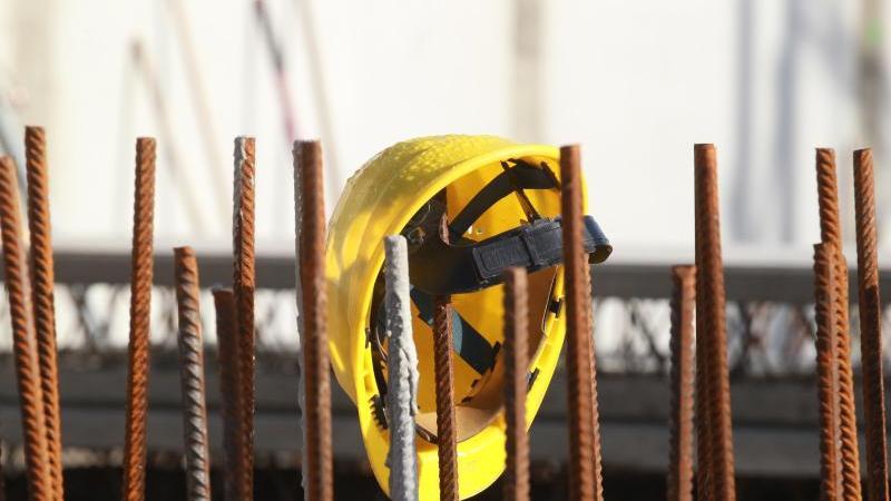 Ein Bauhelm hängt an Fundament-Stangen auf einer Baustelle. Foto: Bodo Schackow/zb/dpa/Archivbild