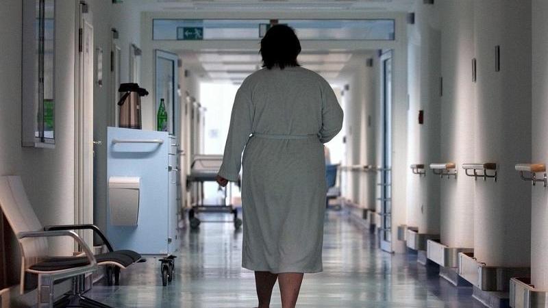 Eine Patientin geht durch einen Krankenhausflur. Foto: Peter Endig/dpa-Zentralbild/dpa/Archivbild