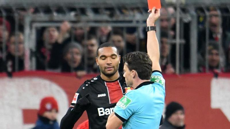 Der Schiedsrichter Guido Winkmann zeigt die rote Karte gegen Jonathan Tah von Leverkusen. Foto: Tobias Hase/dpa