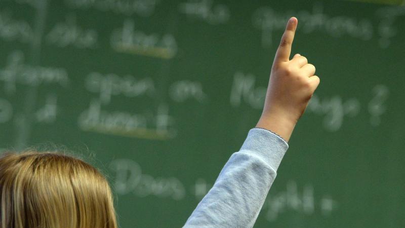 Eine Schülerin meldet sich in einem Klassenzimmer während des Englischunterrichts. Foto: Marijan Murat/dpa/Archivbild
