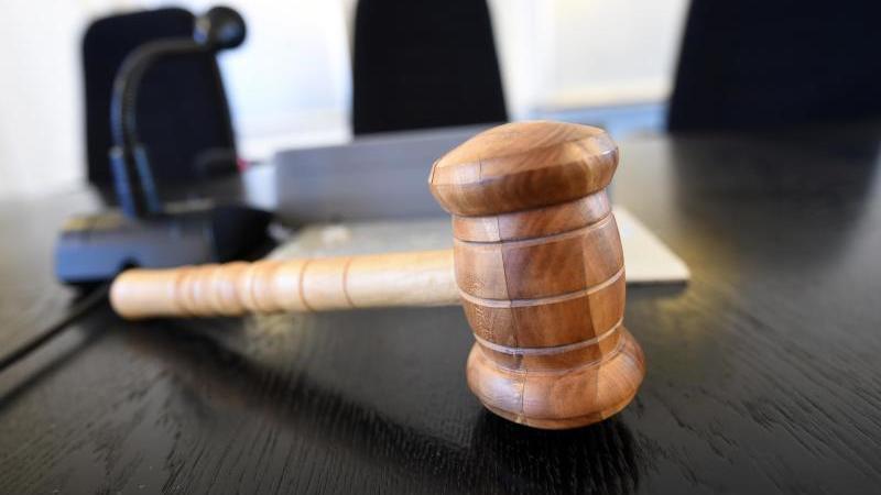 Auf einer Richterbank liegt ein hölzener Richterhammer. Foto: Uli Deck/dpa/Archivbild