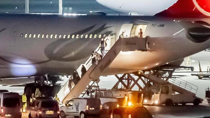 Aus der Türkei abgeschobene Personen werden am Flughafen Tegel von der Polizei in Empfang genommen. Foto: Christoph Soeder/dpa/Archiv