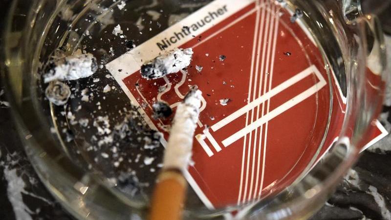 Eine Zigarette verglimmt in einem Aschenbecher. Foto: Helmut Fohringer/APA/dpa/Archivbild