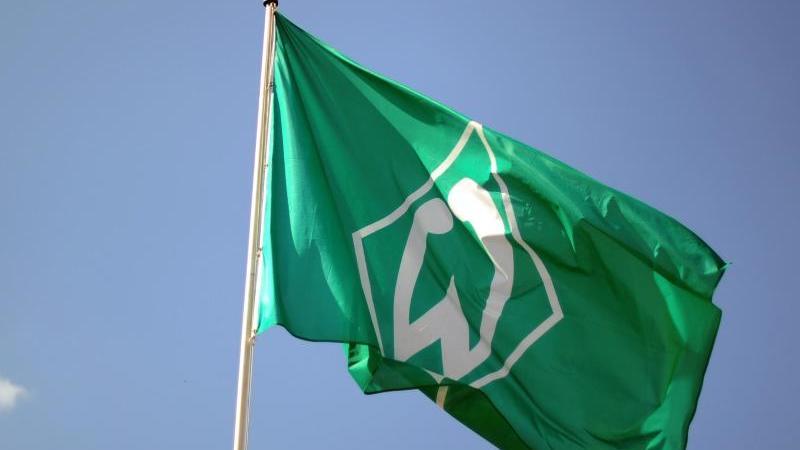 Eine Werder Bremen Fahne weht vor blauem Himmel. Foto: Daniel Reinhardt/dpa/Archivbild