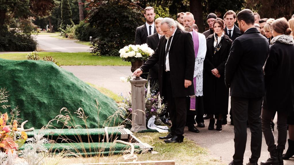 Die Trauergemeinde um Robert (Luca Maric, M.) erweist Irene die letzte Ehre. Die Verwendung des sendungsbezogenen Materials ist nur mit dem Hinweis und Verlinkung auf TVNOW gestattet.