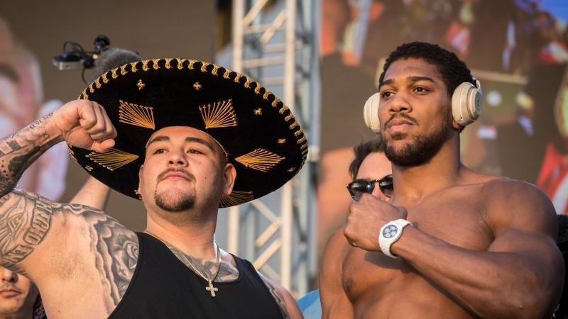 Box-Weltmeister Andy Ruiz (l) und sein Herausforderer Anthony Joshua beim Wiegen. Foto: Oliver Weiken/dpa