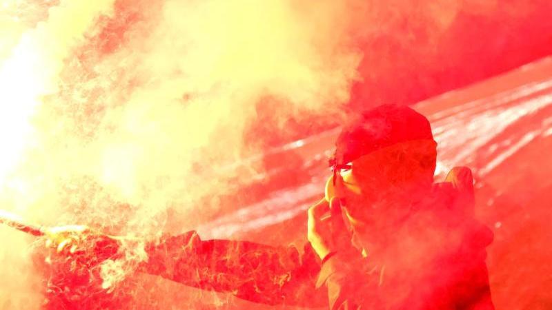 """Ein Fußballfan hält ein brennenden """"Bengalisches Feuer"""" in der Hand und verdeckt sein Gesicht. Foto: Peter Steffen/dpa/Archivbild"""