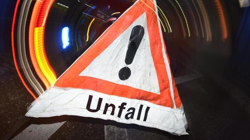 """Ein Warndreieck mit dem Schriftzug """"Unfall"""" steht vor einem Blaulicht auf der Straße. F. Foto: Patrick Seeger/dpa"""