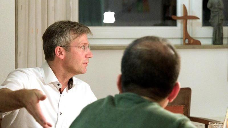 Ein zum Christentum übergetretener Flüchtling spricht mit dem evangelischen Pfarrer Joachim Scheuber. Foto: Matthias Nguyen/dpa