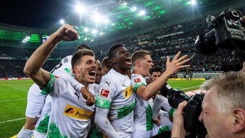 Die Gladbacher Spieler feiern den Treffer zum 2:1 gegen den FC Bayern München durch Ramy Bensebaini (r). Foto: Marius Becker/dpa