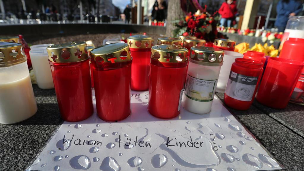 """09.12.2019, Bayern, Augsburg: """"Warum töten Kinder?"""" steht am Königsplatz auf einem Zettel zwischen Grablichtern zu lesen. Ein Feuerwehrmann war am Freitagabend (06.12.2019) hier in seiner Freizeit nach einem Schlag so schwer verletzt worden, dass er"""