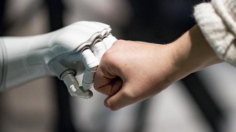 Ein Roboter interagiert mit einer Frau. Foto: Axel Heimken/dpa/Archivbild