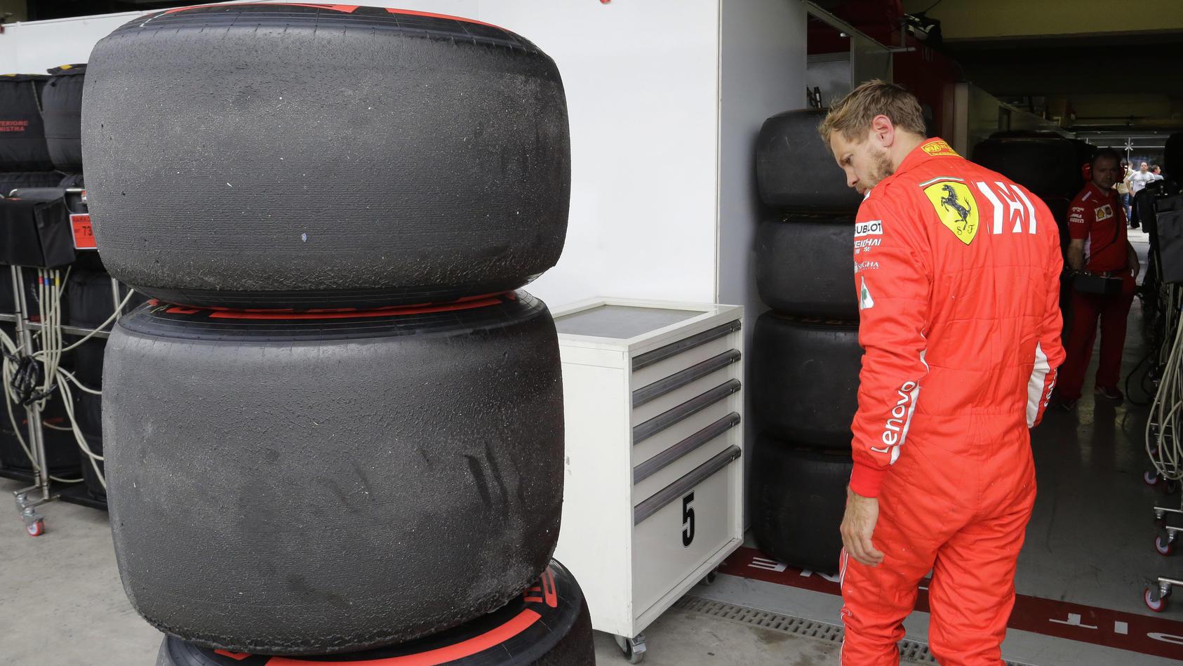Vettel bestaunt die neuen alten Reifen