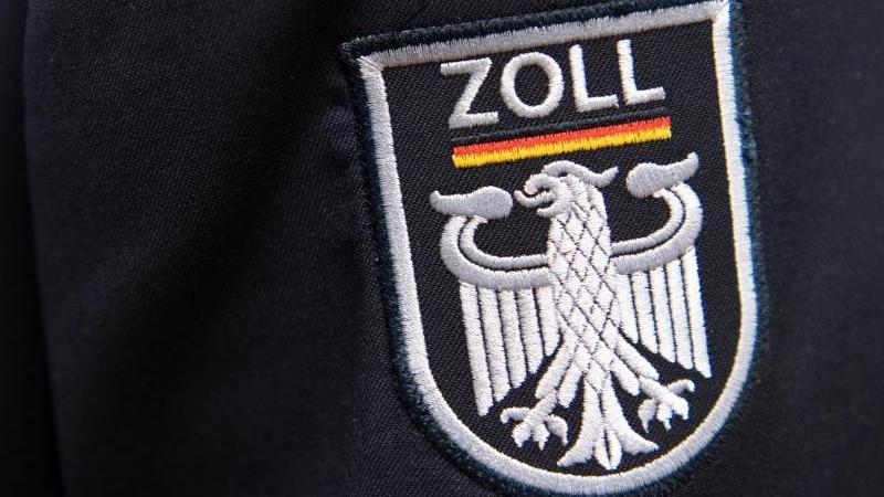 Das Logo der deutschen Zollbehörde befindet sich an einer Uniform. Foto: Ralf Hirschberger/dpa/Archivbild