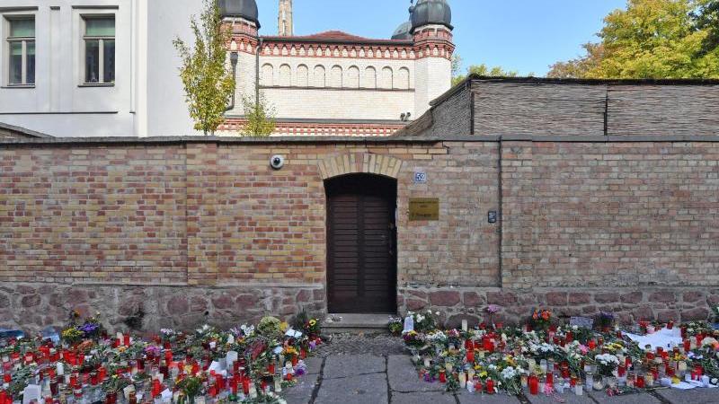 Blumen und Kerzen stehen neben der Tür zur Synagoge, vier Tage nach dem Anschlag auf die Gemeinde. Foto: Hendrik Schmidt/zb/dpa/Archivbild