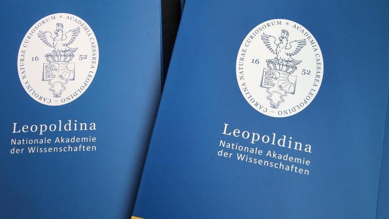 Informationsmappen von der Nationalen Akademie der Wissenschaften Leopoldina liegen auf einemTisch. Foto: Wolfgang Kumm/dpa/Archivbild