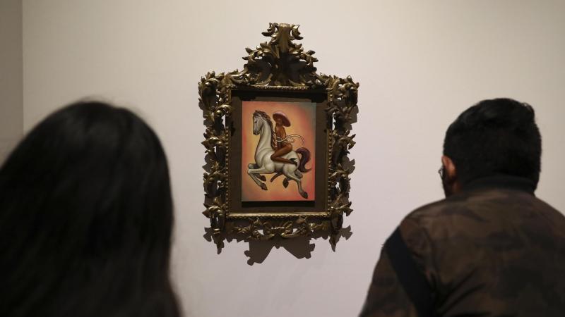 Besucher beobachten ein Gemälde, auf dem der mexikanischen Nationalheld Emiliano Zapata nackt und mit hochhackigen Schuhen dargestellt wird. Foto: Eduardo Verdugo/AP/dpa