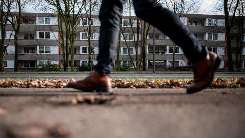 Ein Mann geht an einem Wohnblock vorbei. Foto: Fabian Strauch/dpa/Archivbild