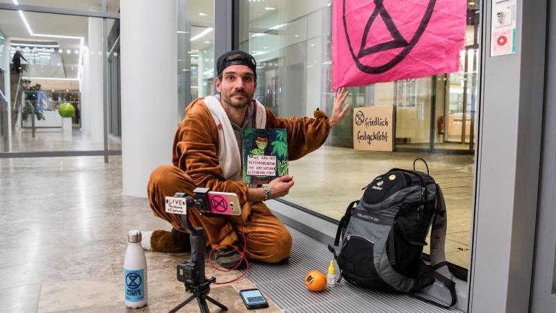 Extinction-Rebellion-Aktivist Thomas Nier klebt mit der Hand an einer Scheibe der Siemens Zentrale. Foto: Matthias Balk/dpa