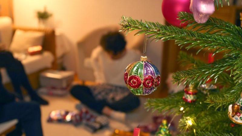 Eine Junge packt hinter einem geschmücktem Christbaum Weihnachtsgeschenke aus. Foto: Karl-Josef Hildenbrand/dpa