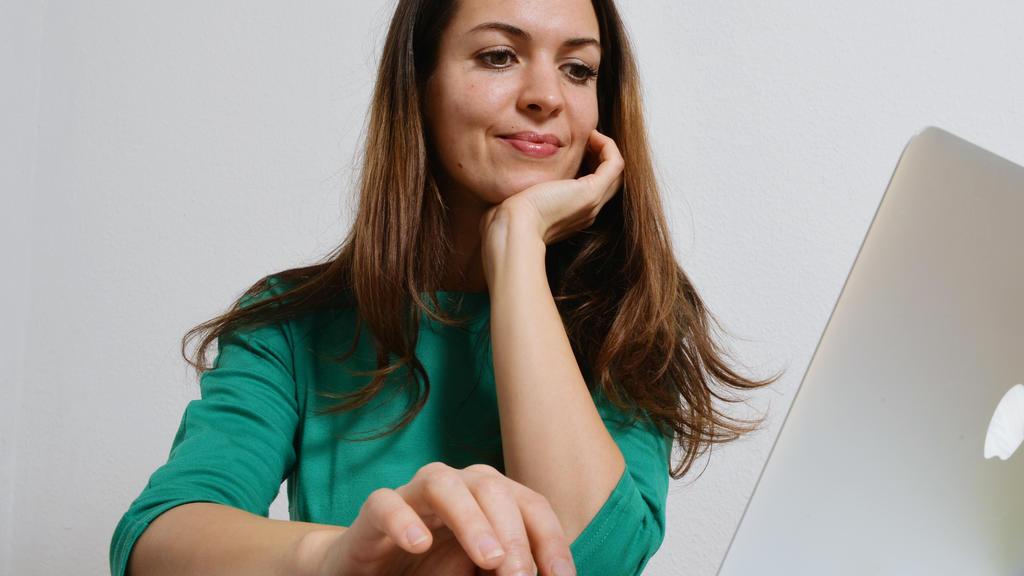 Eine junge Frau sitzt an einem Laptop,