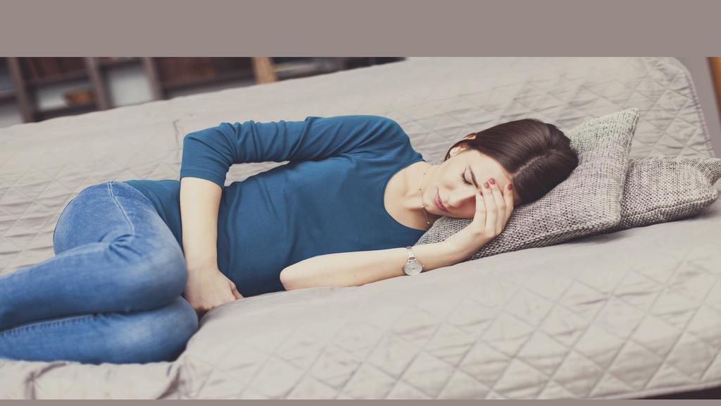 Frau liegt mit Bauchschmerzen auf dem Sofa