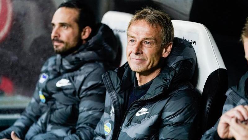 Berlins Trainer Jürgen Klinsmann (M) sitzt neben Berlins Co-Trainer Alexander Nouri (l) auf der Bank. Foto: Uwe Anspach/dpa/Archivbild