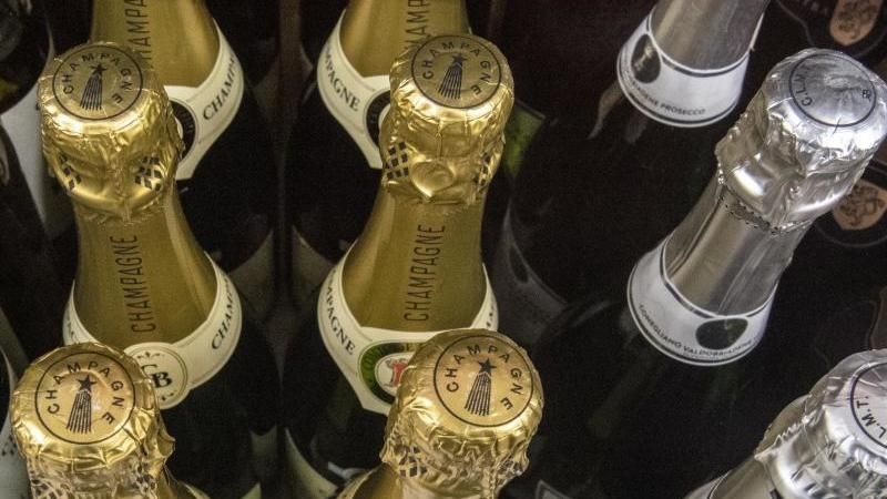 Champagner-Flaschen: Rechtzeitig zum Weihnachtsfest schmücken auch Deutschlands Discounter ihre Filialen mit einem Hauch von Luxus. Foto: Paul Zinken/dpa