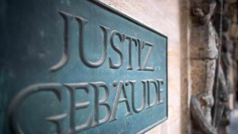 """Ein Schild mit der Aufschrift """"Justizgebäude"""" hängt am Eingang. Foto: Daniel Karmann/dpa/Archivbild"""