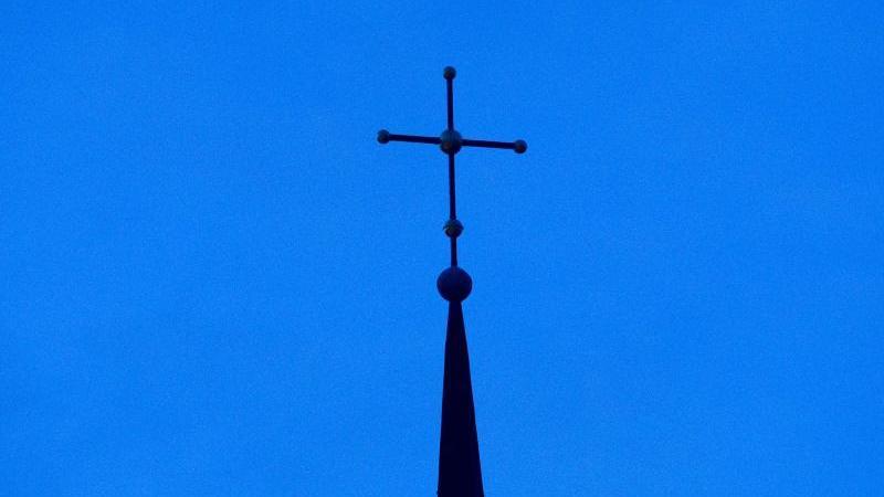 Das Kreuz einer evangelisch-lutherischen Kirche ist in der Abenddämmerung zu sehen. Foto: Friso Gentsch/dpa/Archivbild