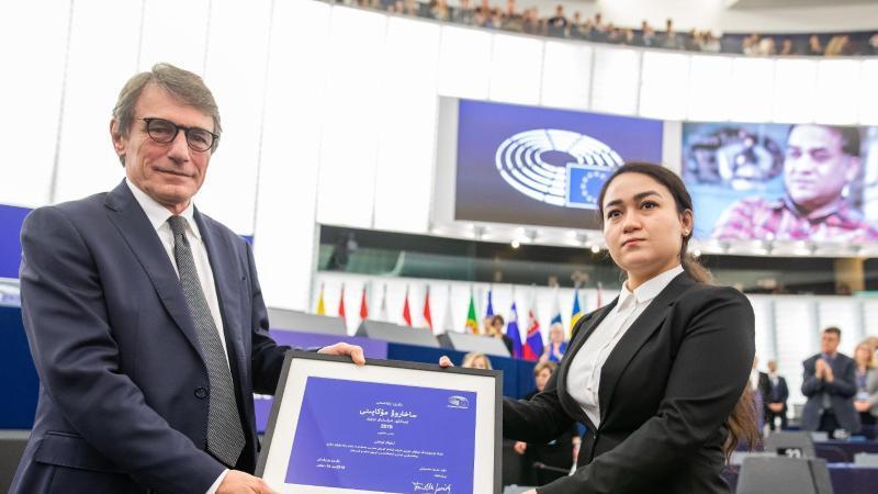Jewher Ilham nimmt für ihren Vater den Sacharow-Preis aus den Händen des Präsidenten des Europäischen Parlaments, David Sassoli, entgegen. Im Hintergrund ist ein Foto von Ilham Tohti zu sehen. Foto: Philipp von Ditfurth/dpa