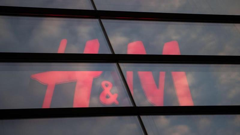 Das Logo des Textilhandelsunternehmens H&M (Hennes & Mauritz) ist hinter einer Scheibe zu sehen. Foto: Marijan Murat/dpa/Archivbild