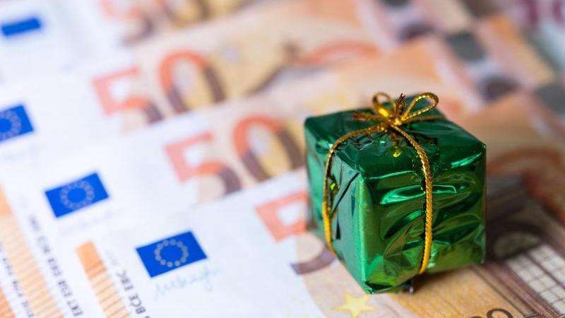 Ein kleines Geschenk liegt auf Banknoten. Foto: Monika Skolimowska/Archivbild