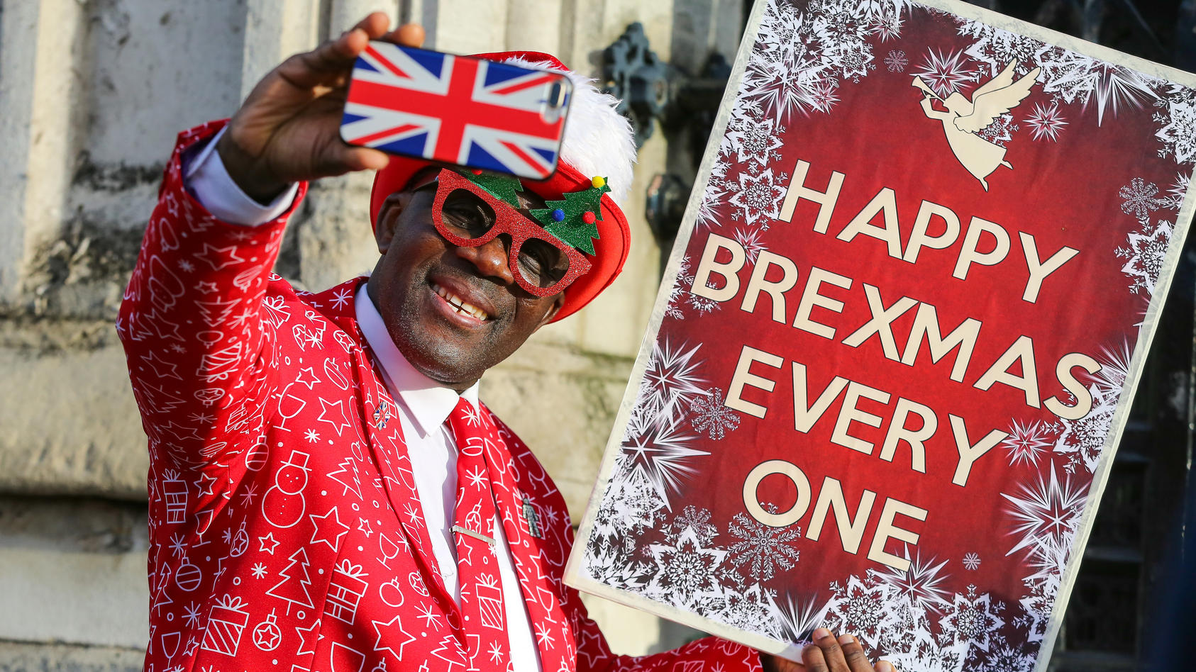 December 18, 2019, London, UK, UK: London, UK. A Pro-Brexit supporter takes a selfie while holding a HAPPY BREXMAS EVERY