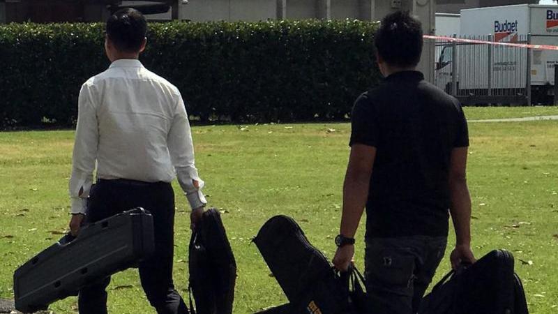 Zwei Männer mit Sporttaschen bringen Waffen ins Vereinsheim des Rugby-Clubs im Vorort Manurewa (Archiv). Foto: Christoph Sator/dpa