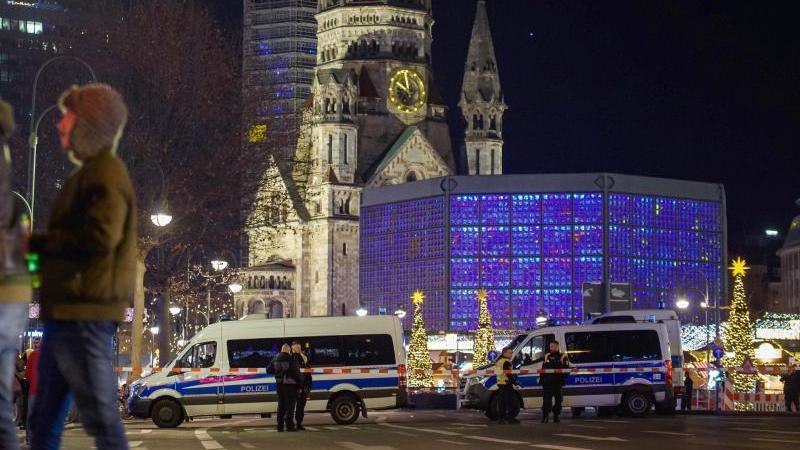 Polizisten stehen vor dem geräumten Berliner Weihnachtsmarkt. Foto: Gregor Fischer/dpa