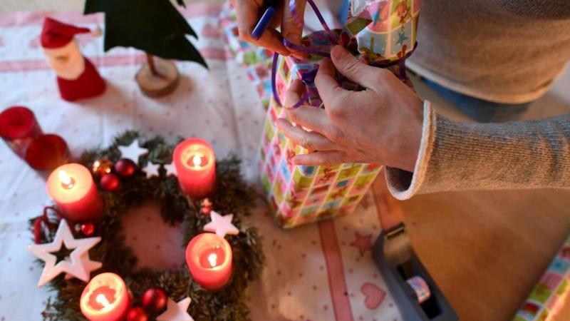 Eine Frau packt am vierten Advent Weihnachtsgeschenke ein. Foto: Angelika Warmuth/dpa
