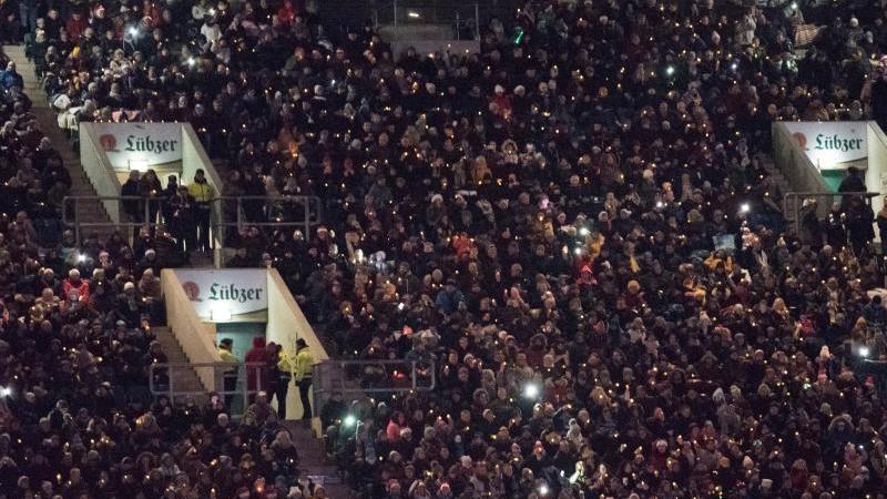Menschen stehen zum gemeinsamen Weihnachtssingen im Ostseestadion. Foto: Frank Hormann/dpa
