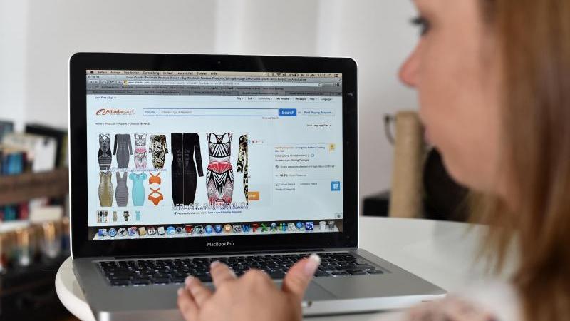 Eine junge Frau surft auf der Internetseite des chinesischen Onlinehändlers Alibaba. Foto: Jens Kalaene/dpa-Zentralbild/dpa