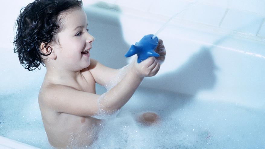 Ein Kind sitzt in der Badewanne.