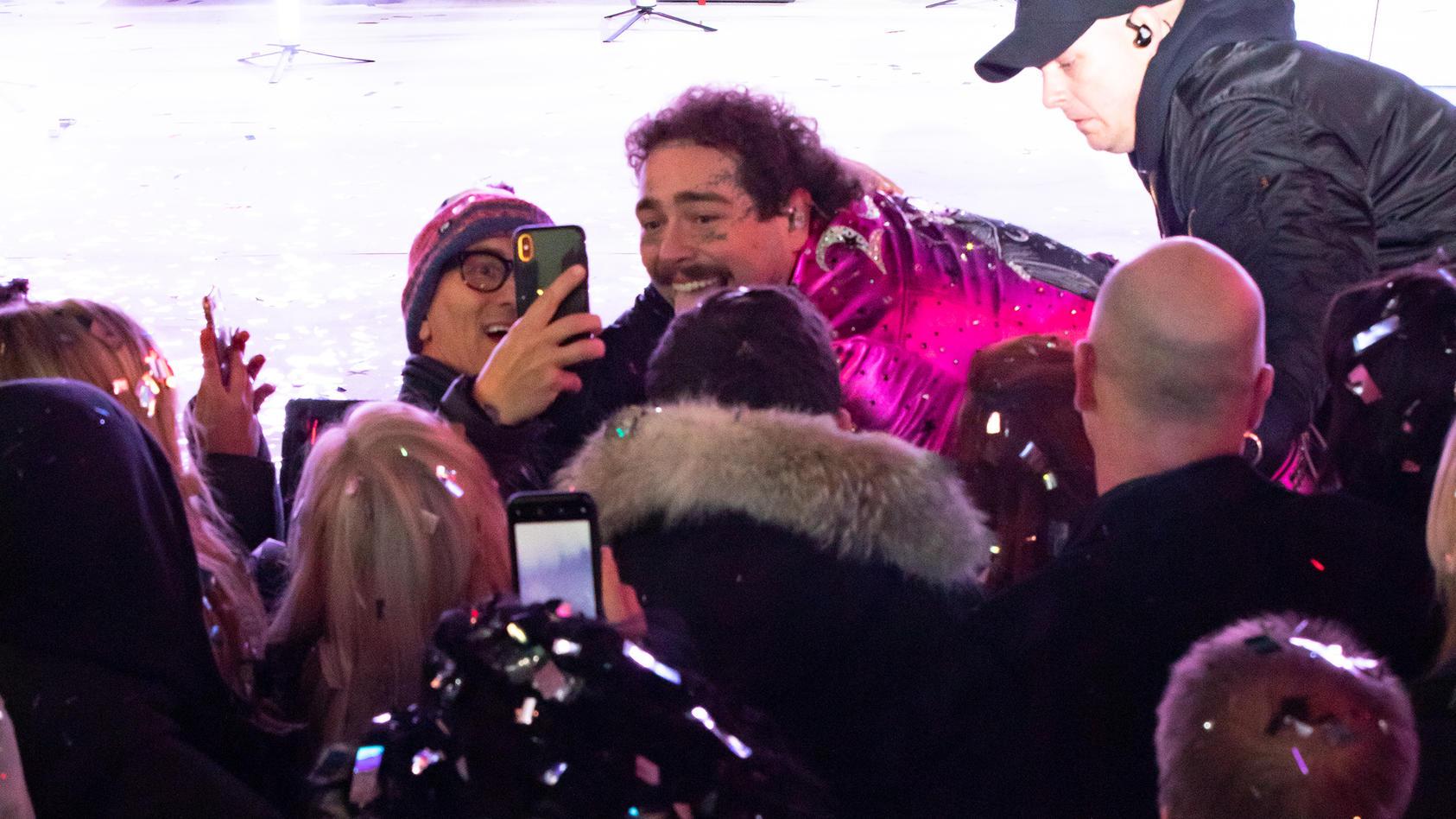 Post Malone kracht von der Bühne und macht erstmal ein Selfie mit einem Fan.