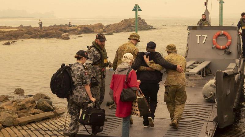 In der Küstenstadt Mallacoota bringt die Marine Menschen in Sicherheit, die sich an den Strand gerettet hatten. Foto: Pois Helen Frank/Royal Australian Navy/AP/dpa