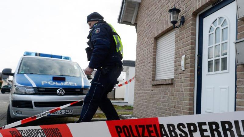 Ein Polizist das ein Haus, in dem drei Leichen gefunden worden waren. Foto: Roberto Pfeil/dpa