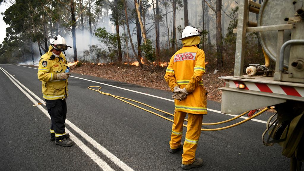 Firefighters keep a watchful eye on a fire threatening homes along the Princes Highway near in Milton, Australia January 5, 2020. REUTERS/Tracey Nearmy