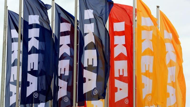 Fahnen wehen vor einem Möbelhaus von Ikea. Foto: Peter Gercke/zb/dpa