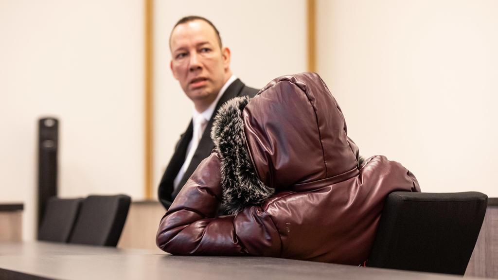 07.01.2020, Nordrhein-Westfalen, Duisburg: Einer der bei der Vergewaltigung einer jungen Frau mutmaßlich beteiligten Jugendlichen (r) sitzt mit einer Kapuze über dem Kopf im Gerichtssaal neben Marc Decker, seinem Anwalt. Fünf Jugendliche sollen in Mü