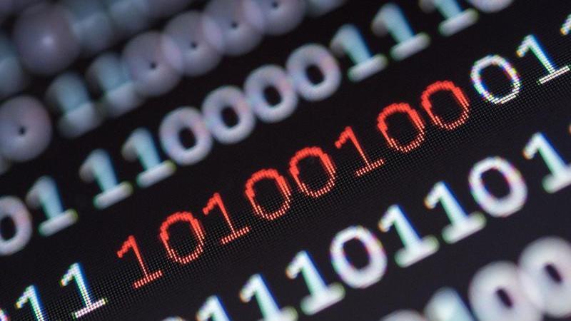 Ein Binärcode, von dem ein Segment rot eingefärbt ist, steht auf einem Bildschirm. Foto: Sebastian Gollnow/dpa/Symbolbild