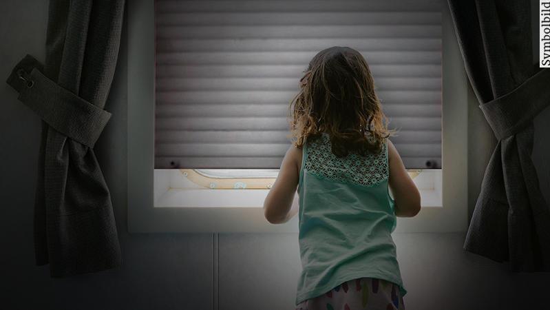 Mädchen vor geschlossenem Fenster (Symbolbild).