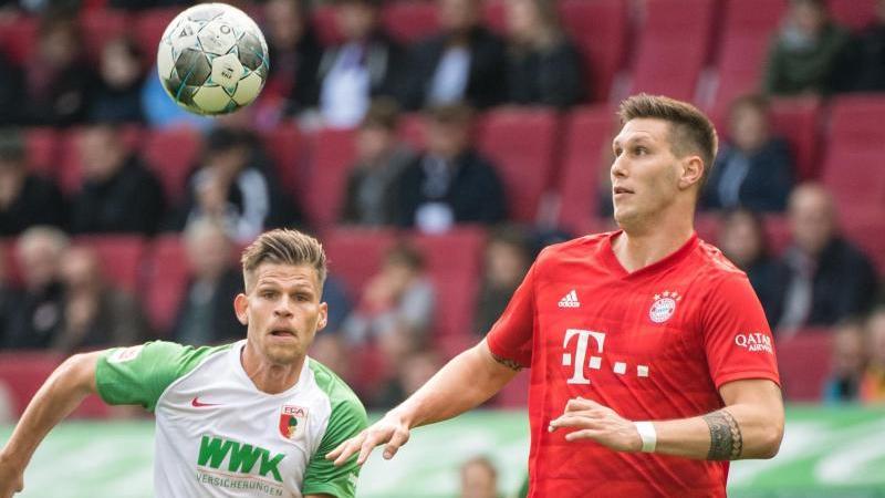 Niklas Süle vom FC Bayern München (r) im Zweikampf mit Florian Niederlechner von Augsburg um den Ball. Foto: Matthias Balk/dpa/Archivbild