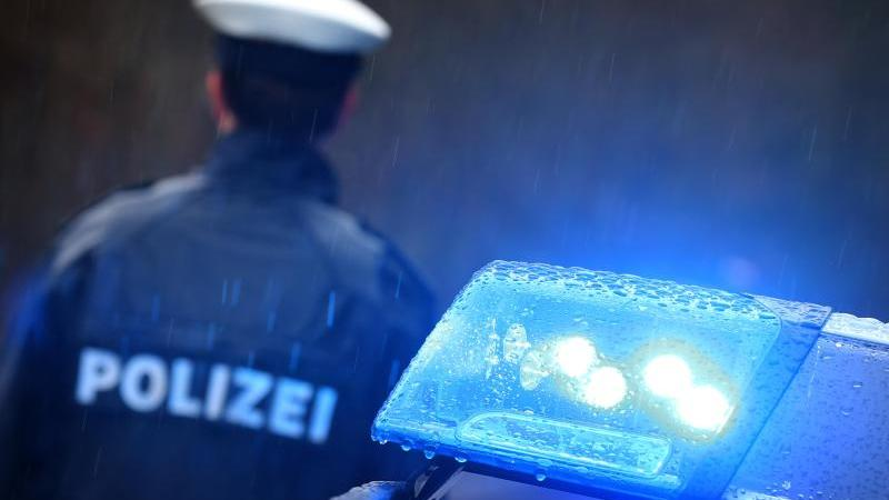 Ein Polizist steht im Regen vor einem Streifenwagen dessen Blaulicht aktiviert ist. Foto: Karl-Josef Hildenbrand/Archiv